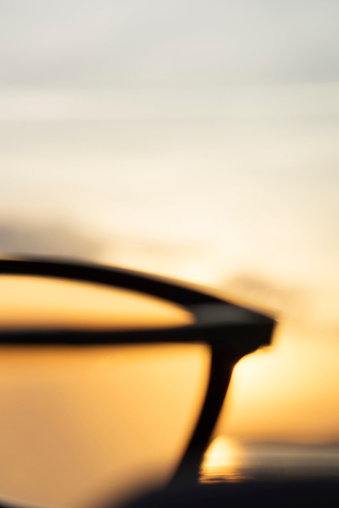 Eyesight「A series of abstract images of black rimmed reading glasses at sunset with selective focus」:スマホ壁紙(17)