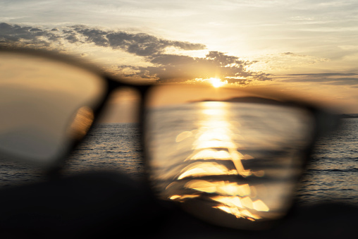 Eyesight「A series of abstract images of black rimmed reading glasses at sunset with selective focus」:スマホ壁紙(3)