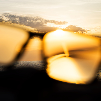 Eyesight「A series of abstract images of black rimmed reading glasses at sunset with selective focus」:スマホ壁紙(1)
