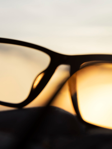 Eyesight「A series of abstract images of black rimmed reading glasses at sunset with selective focus」:スマホ壁紙(19)