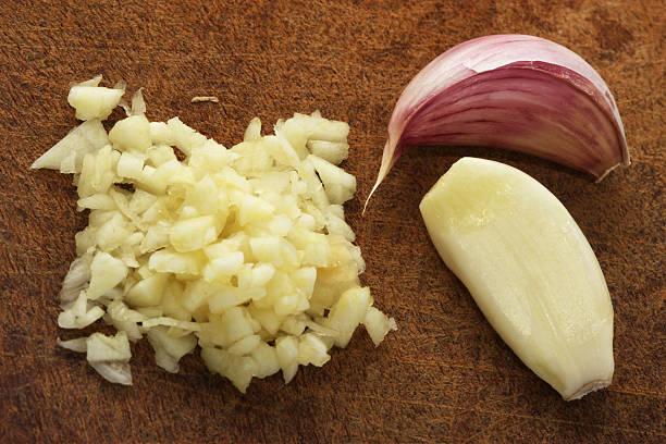 Finely chopped garlic on a wooden cutting board:スマホ壁紙(壁紙.com)