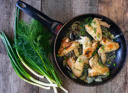 Chicken Wing「Fried chicken wings in frying pan with herbs and spring onions on wooden table」:スマホ壁紙(13)