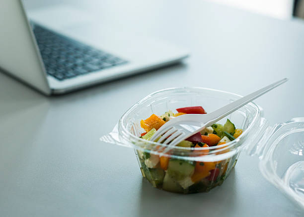 Plastic bowl with salad on desk in office:スマホ壁紙(壁紙.com)