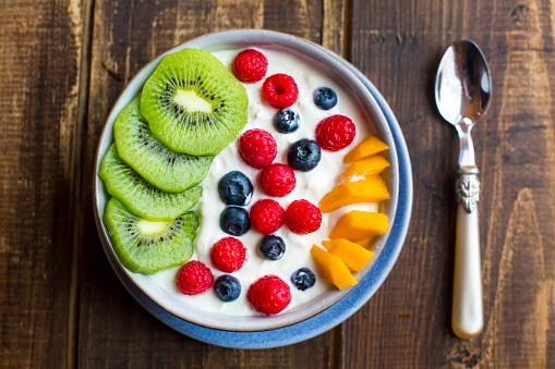 Kiwi「Bowl with yogurt and blueberries, kiwi, mango and raspberries, spoon on wood」:スマホ壁紙(11)