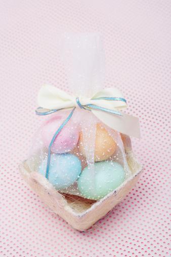 Easter Basket「Mesh bag filled with Easter eggs in basket, elevated view」:スマホ壁紙(1)