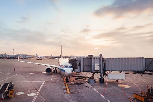 Passenger Boarding Bridge「Airplane parked at gate at airport」:スマホ壁紙(12)