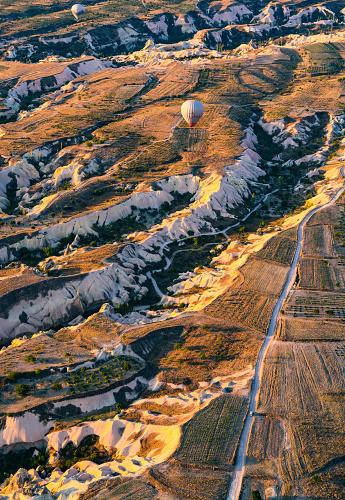 気球「Hot air balloons cruising over road through the hills with one solo car below, Cappadocia, Turkey」:スマホ壁紙(19)