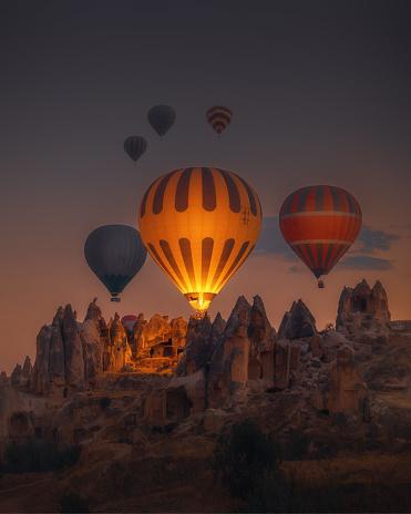 Balloon「Hot Air balloons flying over rock formations at sunrise in Cappadocia, Goreme, Turkey」:スマホ壁紙(5)