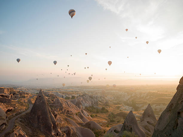 Hot air balloons rise above desert landscape:スマホ壁紙(壁紙.com)