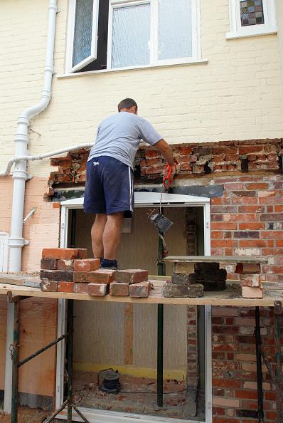 Brick Wall「Man on platform bricklaying at house, UK」:写真・画像(2)[壁紙.com]