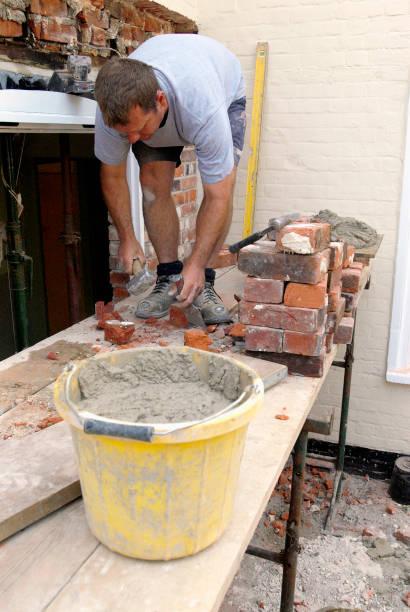 Man on platform bricklaying at house, UK:ニュース(壁紙.com)