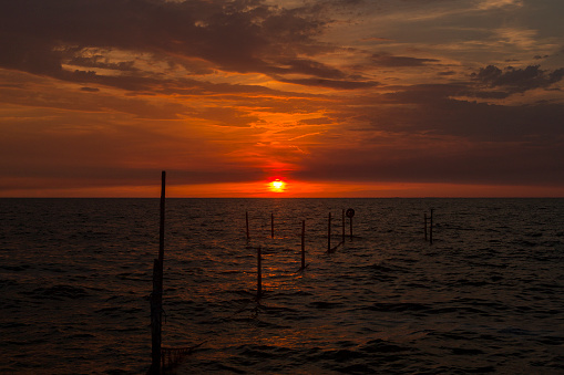 Horizontal「Setting sun above Dutch IJsselmeer with poles of fish trap in foreground」:スマホ壁紙(18)