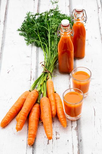 Vegetable Juice「Carrots, glasses of carrot juice and swing top bottles on wood」:スマホ壁紙(0)