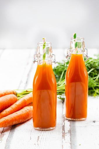 Vegetable Juice「Carrots, glasses of carrot juice and swing top bottles on wood」:スマホ壁紙(12)