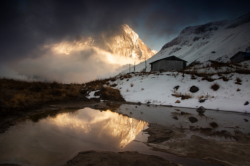 Annapurna Conservation Area「Tin shed and Mt Machhapuchhre reflected in a pond, Annapurna Base Camp at sunset with swirling clouds and light on the mountain peaks, Himalayas, Nepal」:スマホ壁紙(19)