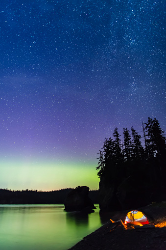 星空「A glowing tent on a beach overlooks green Aurora Borealis reflected in the tranquil ocean water, Hesketh Island」:スマホ壁紙(7)