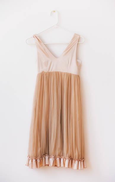 Dress with frill on hanger against white wall:スマホ壁紙(壁紙.com)