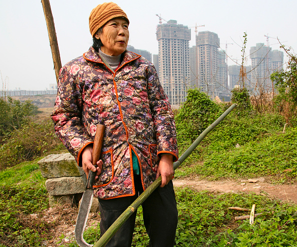 Chongqing「A woman looks out across new residential housing is constructed on farmland in outer Chongqing.」:写真・画像(1)[壁紙.com]