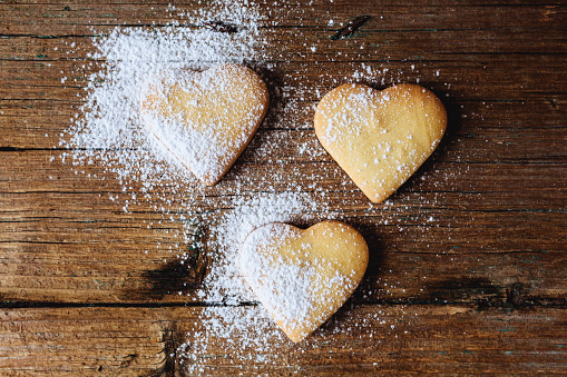 Cookie「Three heart-shaped shortbreads sprinkled with icing sugar on wood」:スマホ壁紙(15)