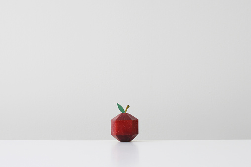 White Background「Red apple crafted into geometric shape imitating paper origami」:スマホ壁紙(0)