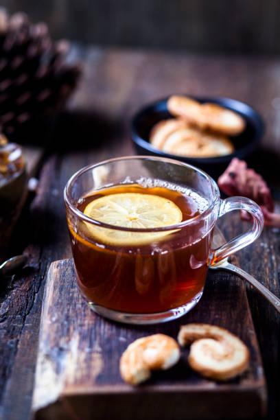 Glass of black tea with slice of lemon and rock sugar on wooden table:スマホ壁紙(壁紙.com)