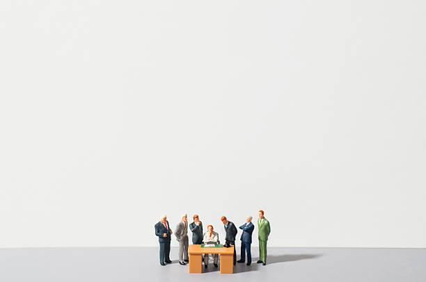 Figurines of people standing around desk:スマホ壁紙(壁紙.com)