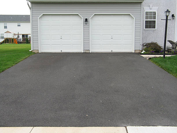 A double garage with white doors at the end of a driveway:スマホ壁紙(壁紙.com)
