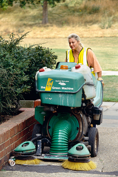 Authority「A woman working for the local authority (or Council) uses a Green Machine to sweep rubbish from a residential area in Greenwich, London, UK」:写真・画像(19)[壁紙.com]