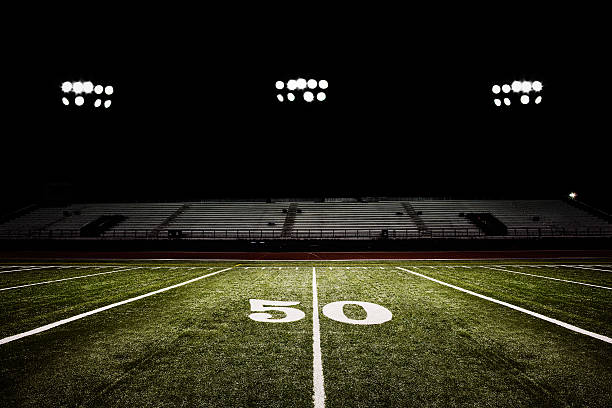 Fifty-yard line of football field at night:スマホ壁紙(壁紙.com)