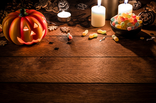 Evil「Jack-o-Lantern pumpkin with copy space on a rustic wooden table」:スマホ壁紙(0)