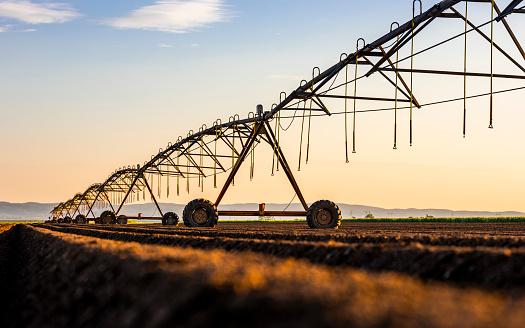 Plowed Field「Irrigation equipment on field against sky during sunset」:スマホ壁紙(11)