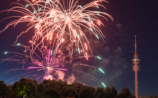 花火「spectacular, majestic fireworks display with colorful starburst explosives exploding in the night sky, rockets shot up bursting, glowing, sparkling and streaking lights during summer festival with Munich's Olympic TV Tower in background illuminated」:スマホ壁紙(13)