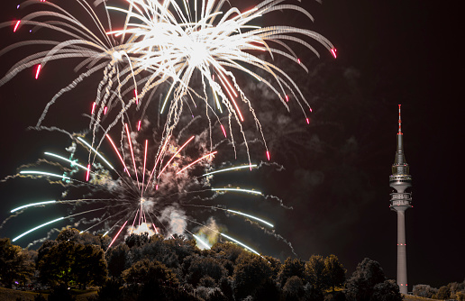 花火「spectacular, majestic fireworks display with colorful starburst explosives exploding in the night sky, rockets shot up bursting, glowing, sparkling and streaking lights during summer festival with Munich's Olympic TV Tower in background illuminated」:スマホ壁紙(10)