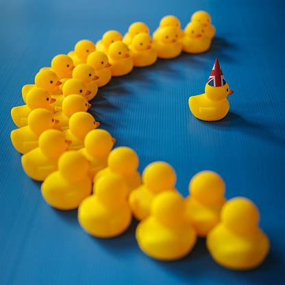 おもちゃのアヒル「ゴム製アヒルのグループからの脱却にユニオン ジャックの帽子と単一の鴨を見て半円に座っています。」:スマホ壁紙(1)