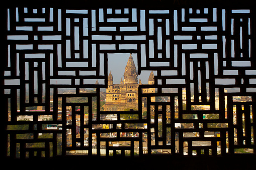 Indian Culture「View of temple through carved stone screen window of Rajput palace」:スマホ壁紙(8)