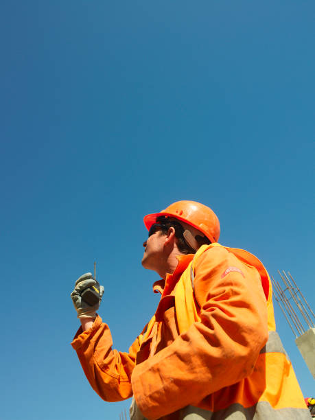 Man looking up and holding walkie talkie, low angle:ニュース(壁紙.com)