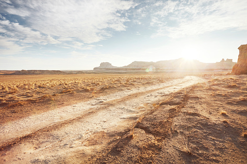 Horizontal「Dirt road in arid desert landscape with distant cliffs and sunlight」:スマホ壁紙(5)