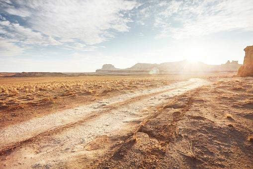 Horizontal「Dirt road in arid desert landscape with distant cliffs and sunlight」:スマホ壁紙(17)