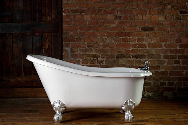 A large claw foot bathtub on a wooden floor:スマホ壁紙(壁紙.com)