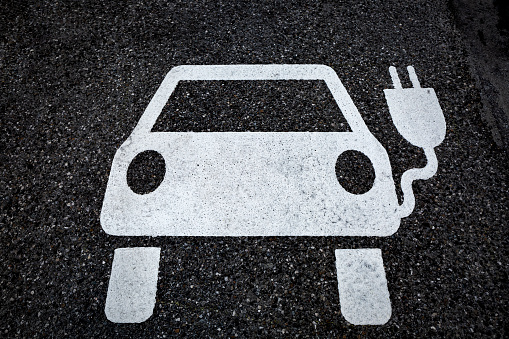 Electronics Industry「Symbol for a charging ststion for electric vehicles on tarmac」:スマホ壁紙(3)