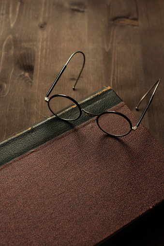 Eyeglasses「Spectacles on a book on wooden table」:スマホ壁紙(1)