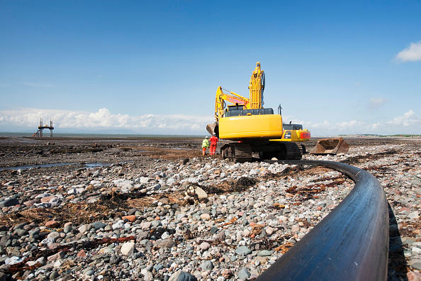 Construction Machinery「Construction workers working on the foreshore of the Solway Firth near Workington, installing the power cable that will carry the electricity from the new Robin Rigg offshore wind farm in the Solway Firth. Robin Rigg is one of the largest wind farms in t」:写真・画像(1)[壁紙.com]
