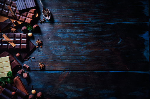 chestnut「Low key image of a variety of chocolate and bombones with dried fruit. Old fashioned style on a blue rustic table with copy space」:スマホ壁紙(6)