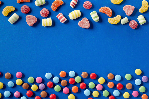 Eating「Colorful candies on bue background, copy space」:スマホ壁紙(3)