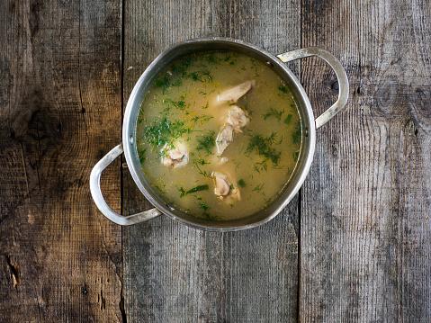 Bouillon「Saucepan of chicken soup on wooden table」:スマホ壁紙(16)