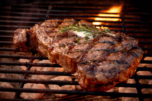 Large Juicy Beef Rib Eye Steak on a Hot Grill with Charcoal and Flames:スマホ壁紙(壁紙.com)