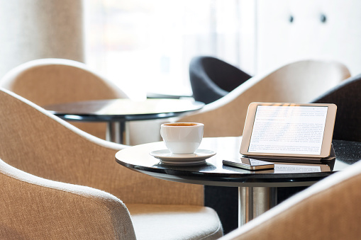 Convenience「Digital tablet, smartphone and cup of coffee on table in hotel lobby」:スマホ壁紙(8)