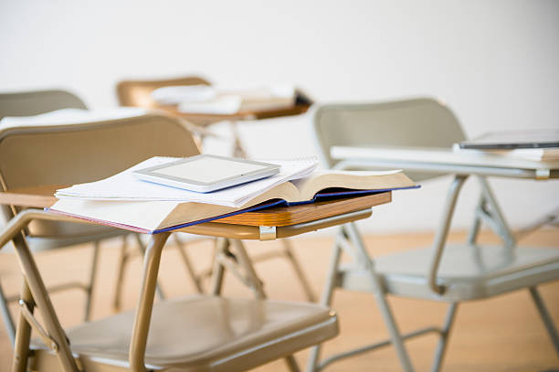 Digital tablet and book on desk in classroom:スマホ壁紙(壁紙.com)