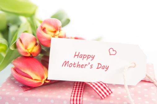 母の日「Bouquet of tulips next to a gift with a happy mothers day card」:スマホ壁紙(0)