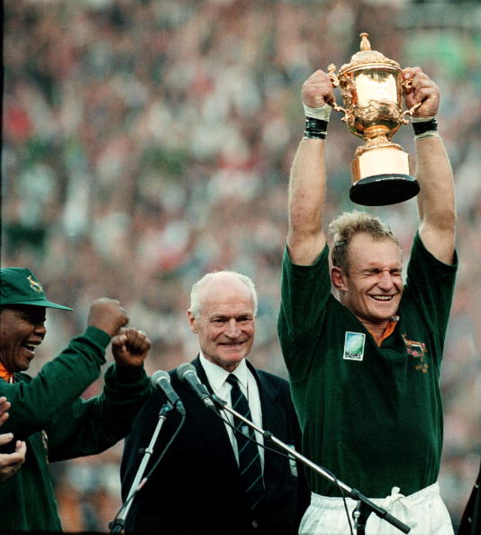 South Africa National Team「South Africa. Captain of the Springbok team, Francois Pienaar holds the Web Ellis trophy up high after defeating the All Blacks at the World Cup. President Nelson Mandela dances in joy.」:写真・画像(1)[壁紙.com]